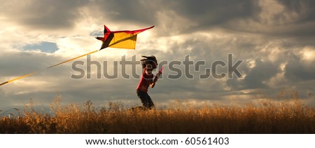 A panorama of a girl happily flying her kite. - stock photo