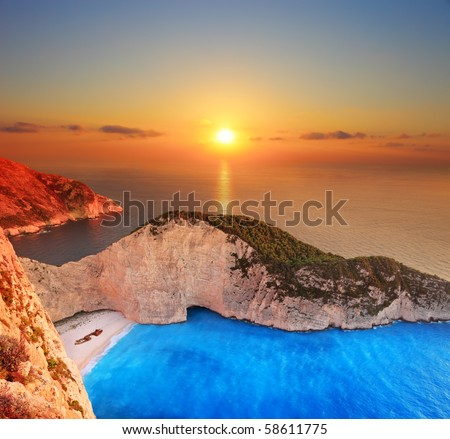 A panorama of sunset over Zakynthos island, Greece with a shipwreck on the sandy beach - stock photo
