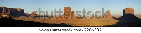 A panorama of West and East Mitten Buttes, Merricks Buttes, and a visitor center lit by setting sun. - stock photo