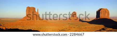 A panorama shot of West Mitten, Last Mitten and Merrick Buttes lit by the sunset sun in Monument Valley (Navajo Nation). - stock photo