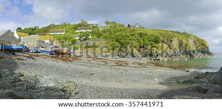 A panorama view of fishing boats moored on the beach at Cadgwith Cove in late summer at low tide, Cornwall, England, UK - stock photo