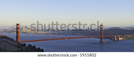 A panoramic image of Golden Gate Bridge lit by the setting sun with the San Francisco skyline in the background.