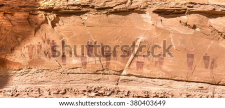 A panoramic image of the Great Gallery of Barrier Canyon petroglyphs in the remote Horseshoe Canyon Unit of Canyonlands National Park, Utah. - stock photo