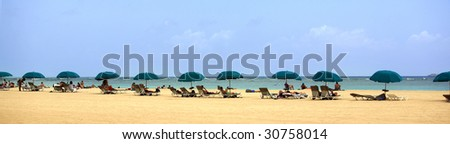 A panoramic shot of a beach with umbrellas