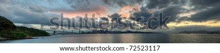 A panoramic skyline of San Francisco with a colorful sunset. - stock photo