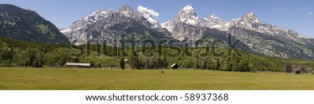 A panoramic view of a horse ranch with the Grand Tetons mountains in the background