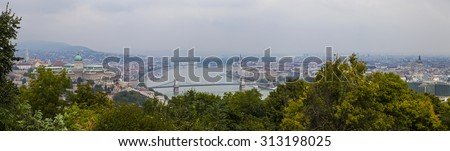 A panoramic view of Budapest from Gellert Hill.  The view takes in many sights including the Hungarian Parliament Building, Buda Castle, Matthias Church, St. Stephens Basilica and the River Danube. - stock photo