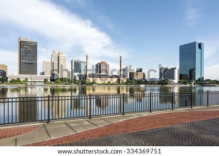 A  panoramic view of downtown Toledo Ohio's skyline from across the Maumee river at a popular restaurant area.  A beautiful  blue sky with white clouds for a backdrop. - stock photo