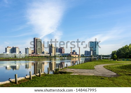 A panoramic view of downtown Toledo Ohio's skyline from across the Maumee river at a public park.  A beautiful  blue sky reflecting in the river.  - stock photo