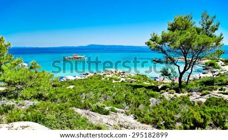 A panoramic view of Portokali (Orange) Beach  in Sithonia, Halkidiki, Greece with a tourist ship. Its original name is Kavourotripes. - stock photo