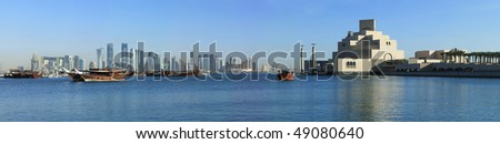 A panoramic view of the skyline of Doha, seen from the corniche with moored dhows and the Museum of Islamic art in the foreground - stock photo