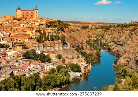 a panoramic view of Toledo, Spain, with the Tagus river in the foreground and the imposing Alcazar in the background - stock photo