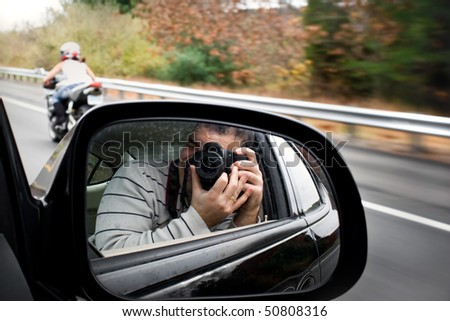 A paparazzi photographer takes a photo of a woman driving a motorcycle on the highway. Shallow depth of field.