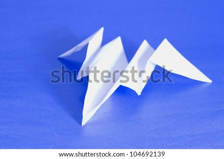 A paper airplane over a blue paper background