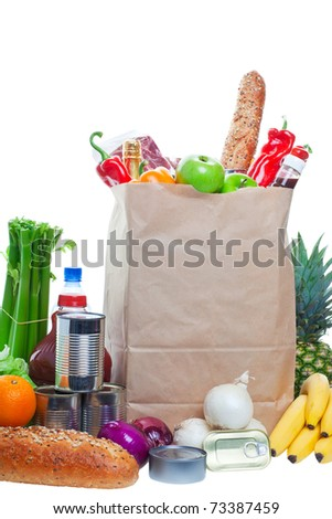 A paper bag full of groceries, surrounded by fruits, vegetables, bread, bottled beverages, and canned goods. Studio isolated on White background - stock photo