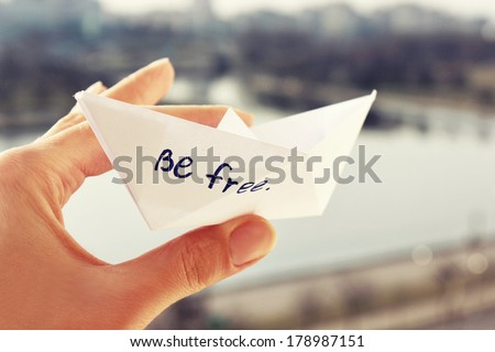 a Paper boat or Be free. Spring and freedom or Paper ship in hand - stock photo