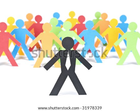 A paper businessman stands out from the multicolored crowd. Selective focus. White background. - stock photo