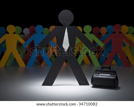 A paper businessman stands under the spotlight in front of multicolor crew. - stock photo