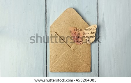 A paper butterfly, cut out of a watercolor toned texture with a handwritten text, on a small recycled paper envelope, shot from above on a light blue wooden board; a template for an invitation design - stock photo