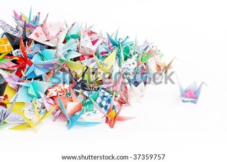 A paper crane standing out from a pile of paper cranes - stock photo