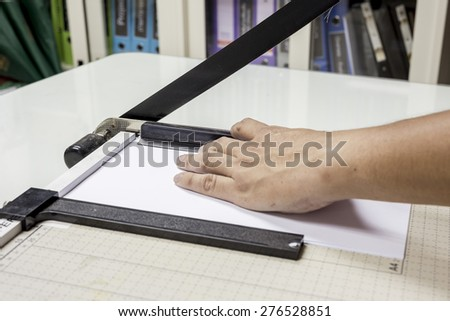 A paper cutter slicing a sheet of paper - stock photo