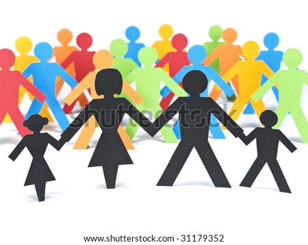 A paper family holding hands in front of a group of multicolor paper men. - stock photo