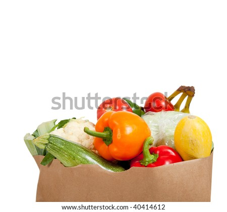 A paper grocery sack with vegetables including peppers, asparagus, celery, tomatoes, squash and broccoli on a white background with copy space - stock photo