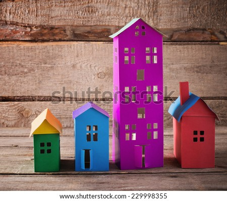 A paper houses stands over a wooden background. - stock photo