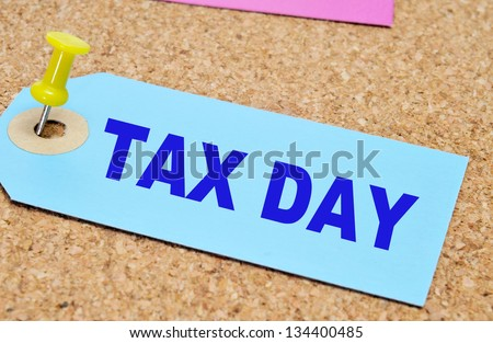 a paper label with the words tax day written on it, pinned with a thumb tack on a cork board - stock photo