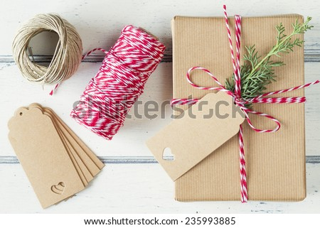A paper parcel with a pine branch, wrapped tied with a tag. Christmas gift box wrapped with paper kraft and tied with red & white baker's twine on a white wooden table. Vintage Style. - stock photo