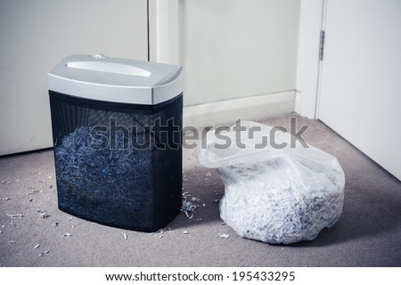 A paper shredder and a bag of shredded documents by the door - stock photo