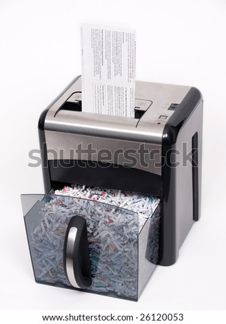 A paper shredder with a confidential document about to be shredded - stock photo