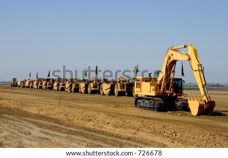 A parade of giant earth-movers are led by a giant mechanical shovel.