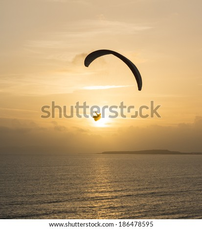 A paraglider flying over the sea at sunset. - stock photo