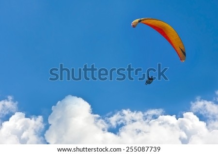 A paraglider gliding over the clouds - stock photo