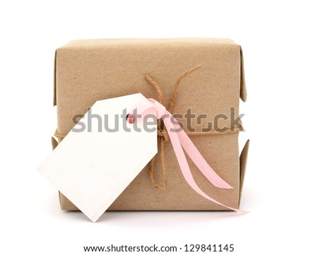 A parcel wrapped in kraft paper and tied with rough twine and white tag - stock photo
