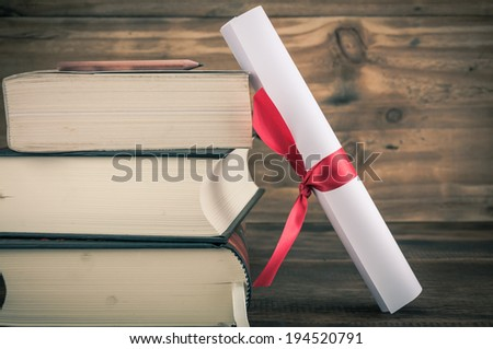 A parchment diploma scroll, rolled up with red ribbon beside a stack of books on wood background with vintage filter - stock photo