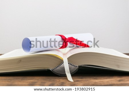 A parchment diploma scroll, rolled up with red ribbon on book on wood background - stock photo