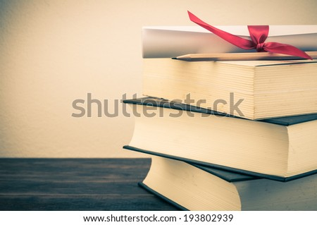 A parchment diploma scroll, rolled up with red ribbon on stack of book on wood background with vintage filter - stock photo