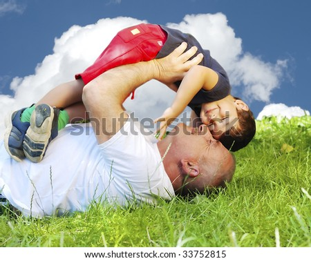 A parent and his kid laying and smiling on grass - stock photo