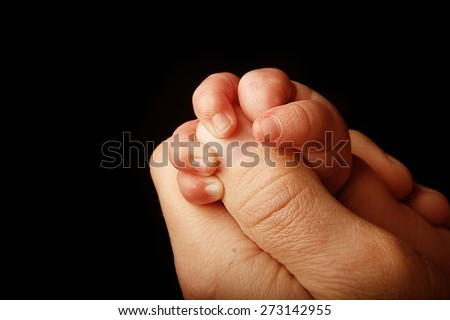 a parent holds the hand of a small child on a black background - stock photo