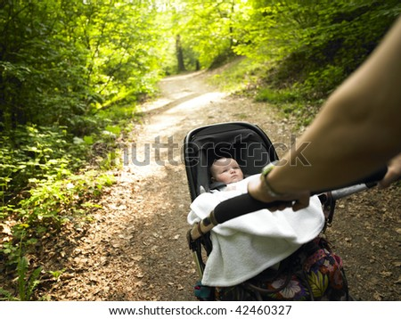 A parent pushes a baby carriage along a wooded path. Horizontally framed shot. - stock photo