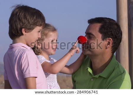 A parent with a clown nose makes your kids laugh - stock photo