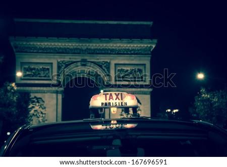 A Parisian taxi near Arc de Triomphe in Paris. Black and white. Toned image. Retro style postcard.  - stock photo