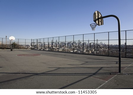 A park basketball court in Jersey City, with the New York skyline visible behind. - stock photo