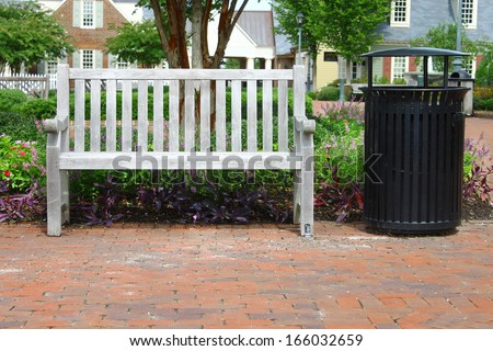 A park bench and a trash can outside among the flowers in Yorktown Virginia on a summer day - stock photo
