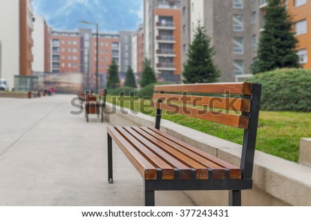 A park bench close in city urban block outside - stock photo