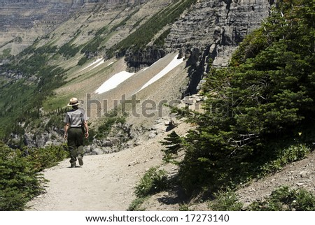 a park ranger walking on Highline Trail in Glacier National Park - stock photo