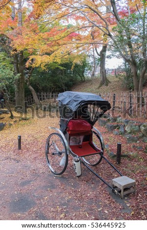 A parked red riksha with autumn leaves