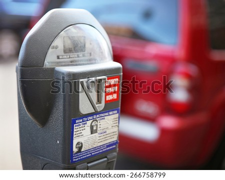 a parking meter with a car in the background on a city street downtown  - stock photo
